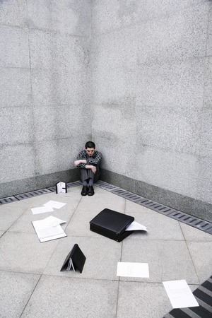 Depressed businessman sitting at the corner of a building Stock Photo