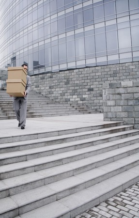Businessman carrying a stack of boxes down the stairs photo