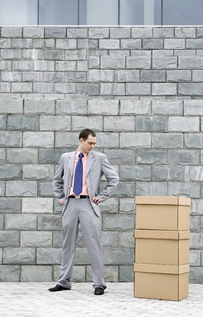 Businessman looking at a stack of boxes photo