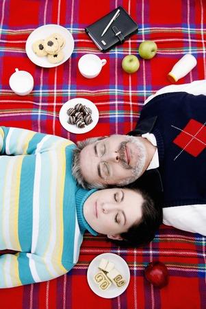 picnic blanket: Pareja acostada sobre una manta de picnic