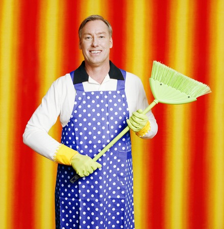 Man in apron holding a broom photo