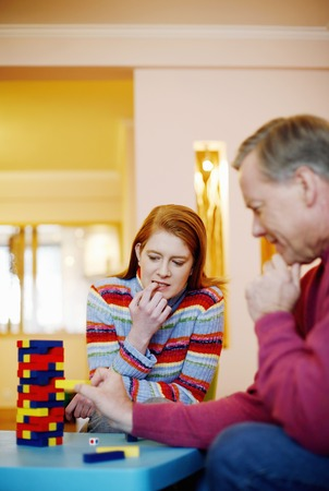 removing the risk: Couple playing block game at home Stock Photo