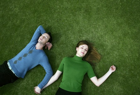 Couple holding hands while lying on the field photo