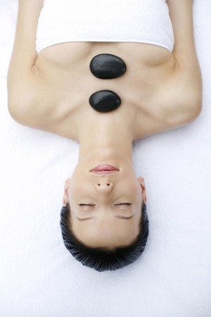 Woman in spa with therapeutic hot stones on body photo