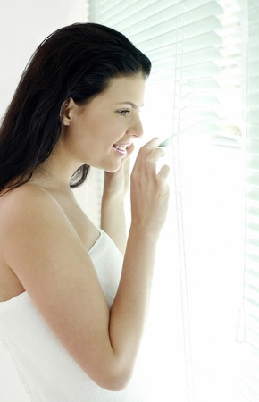 Woman peeking through window blinds photo