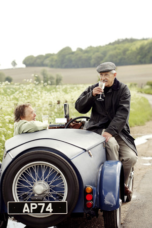 Senior couple drinking wine in the car photo