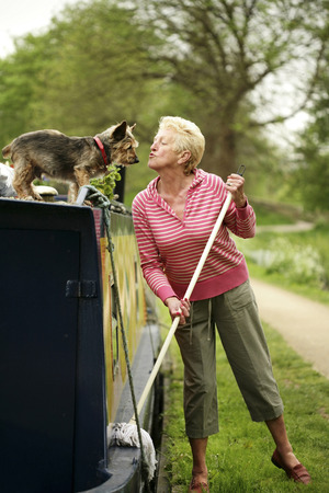 Senior woman playing with her dog while mopping her houseboat photo