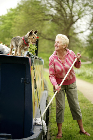 Senior woman looking at her dog while mopping her houseboat photo
