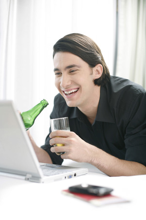 Man drinking beer while using laptop photo