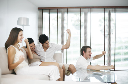 Men and women cheering while watching television at home photo