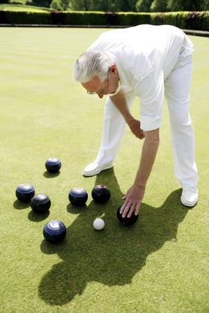 bending down: Man bending down to pick up bowling balls Stock Photo