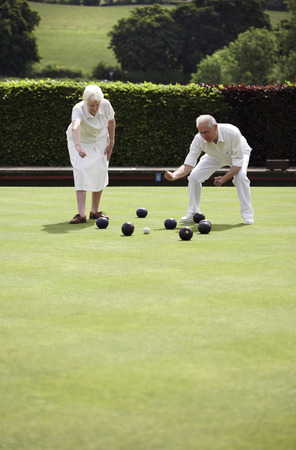 Senior couple lawn bowling in the bowling green photo