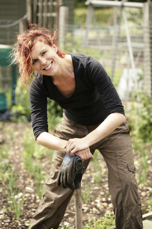 Woman smiling at the camera while gardening in the garden