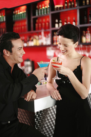 proposing a toast: Couple proposing a toast while drinking in a bar Stock Photo
