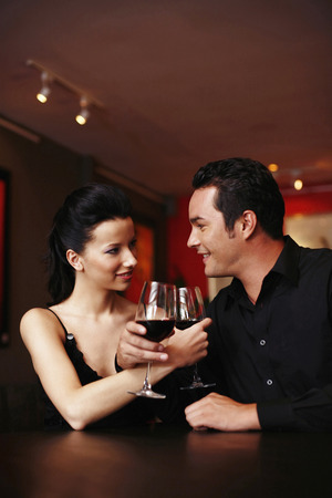Couple locking arms, holding glass of wine photo