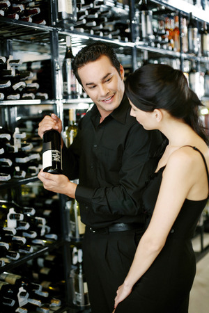 Couple choosing wine at wine cellar photo