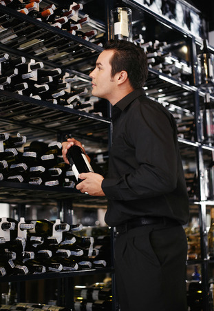 Man choosing wine in the wine cellar photo