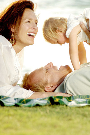 Couple and their lovely daughter having fun in the park photo