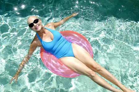 Woman relaxing on inflatable ring in the swimming pool Banco de Imagens