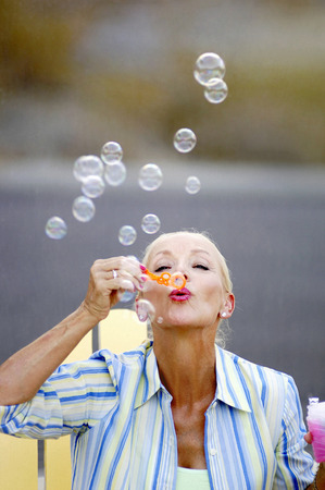 Woman blowing soap bubbles Stock Photo