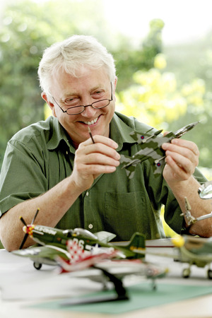 Senior man building model airplane photo