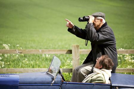Man using binoculars while sitting in the car