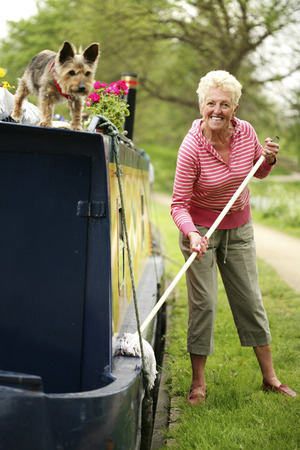 Senior woman mopping houseboat photo