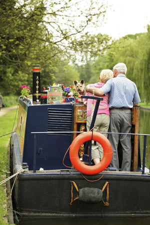 Senior couple and their dog on the houseboat