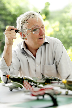 Senior man looking through a magnifying glass photo