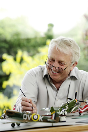 Senior man painting model airplane photo