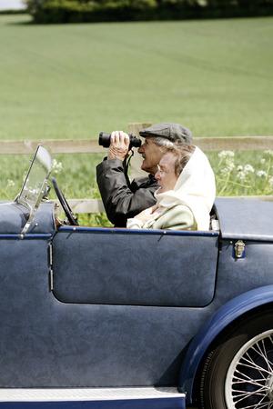 Senior man using binoculars while sitting in the car photo