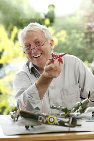 Senior man holding model airplane photo