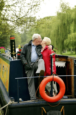 Senior couple kissing on their houseboat photo
