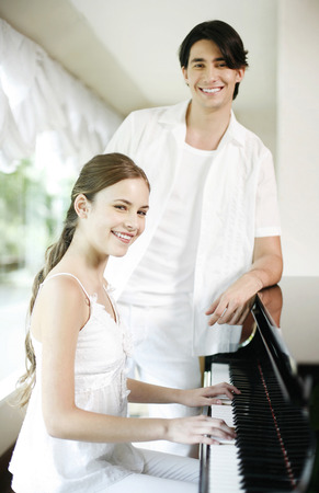 tocando el piano: Mujer tocando el piano con su novio de pie junto a ella Foto de archivo