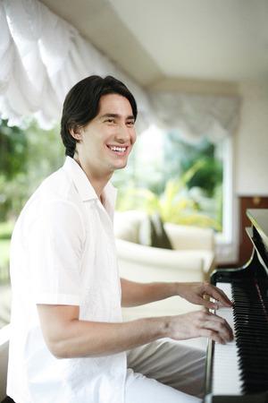 tocando el piano: El hombre sonriente mientras toca el piano Foto de archivo