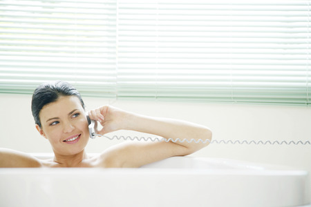 Woman talking on the phone while sitting in the bathtub photo