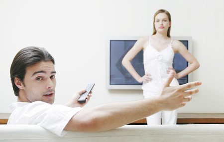 Woman blocking the television while her boyfriend is watching it photo