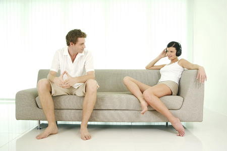 Man looking at his girlfriend listening to music on the headphones photo