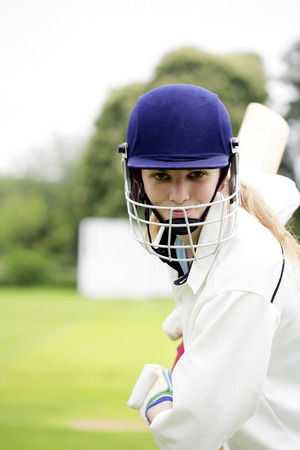 Female cricket player holding a cricket bat Stock Photo
