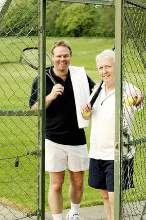 Two men with tennis racquet and tennis ball photo