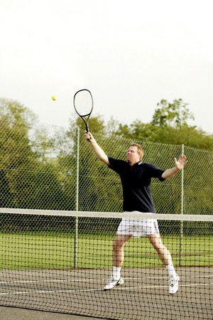 Man playing tennis in the tennis court photo