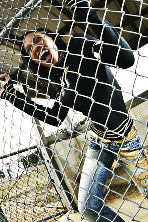 Woman screaming while pulling the fence Imagens
