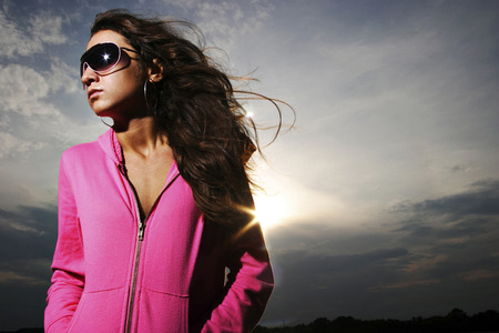 Woman in pink jacket and sunglasses Imagens