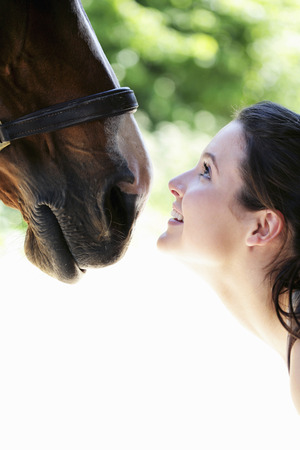 Woman smiling while looking at her horse