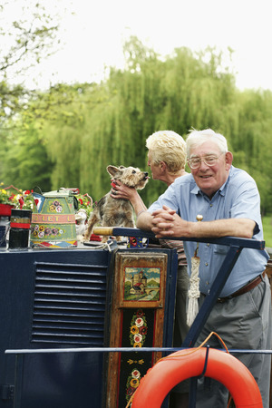 Senior couple and their pet dog on the houseboat photo