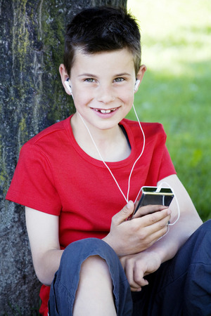 portable mp3 player: Boy leaning against a tree while listening to portable MP3 player