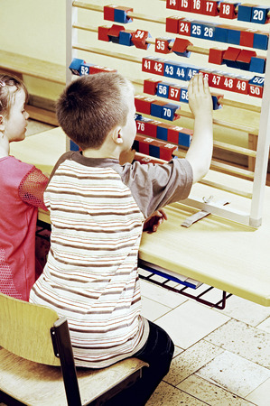 Boy and girl playing with big abacus photo