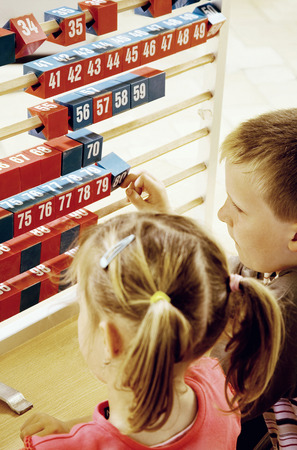 Boy and girl playing with a big abacus photo