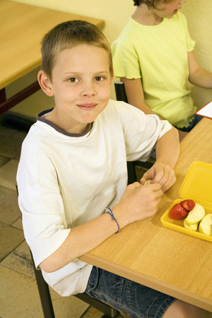 Boy looking at the camera with his lunch box on the table photo