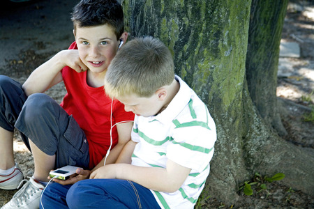 portable mp3 player: Two boys sharing a portable MP3 player